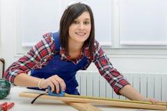 Joli constructeur de fille mesurant une planche de bois image libre de droits