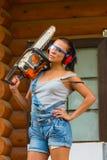 Joli constructeur de jeune femme avec la tronçonneuse actionnée Image libre de droits