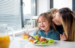 Joli enfant appréciant le baiser de sa maman pendant le repas Photos libres de droits