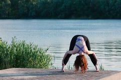 Joli exercice femelle convenable de yoga de pratique dehors photos stock