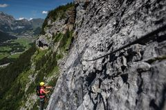 Joli, féminin grimpeur sur a par l'intermédiaire de ferrata photos libres de droits