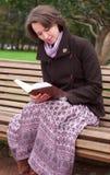 Joli femme affichant un livre sur un banc Images stock