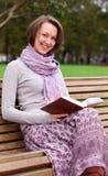 Joli femme affichant un livre sur un banc et un sourire Photographie stock libre de droits