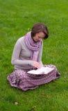 Joli femme affichant un livre sur une herbe Photographie stock libre de droits