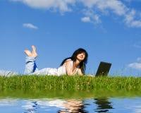 Joli femme avec l'ordinateur portatif Photo stock
