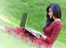 Joli femme avec l'ordinateur portatif sur l'herbe verte à GA Photo stock