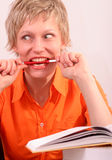Joli femme avec le livre mordant un crayon lecteur image stock