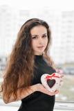Joli femme dans l'amour retenant le cadre en forme de coeur Photographie stock