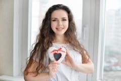 Joli femme dans l'amour retenant le cadre en forme de coeur Photos stock
