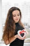 Joli femme dans l'amour retenant le cadre en forme de coeur Photo libre de droits