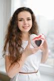 Joli femme dans l'amour retenant le cadre en forme de coeur Image libre de droits