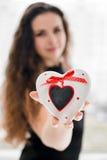 Joli femme dans l'amour retenant le cadre en forme de coeur Images libres de droits