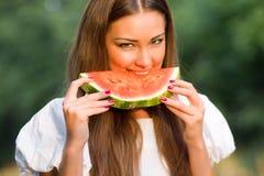 Joli femme mangeant la pastèque extérieure Images stock