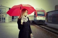 Joli femme près du train se déplaçant dans la gare Photo libre de droits