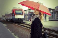 Joli femme près du train se déplaçant dans la gare Photographie stock libre de droits
