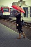 Joli femme près du train se déplaçant dans la gare Photos libres de droits