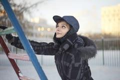Joli femme s'élevant sur l'échelle métallique en hiver Image libre de droits