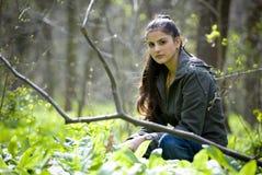 Joli femme s'asseyant dans la forêt Photos stock