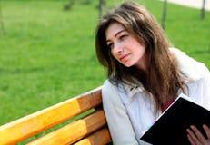Joli femme s'asseyant sur le banc dans le livre du relevé de stationnement Images stock
