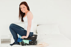 Joli femme s'asseyant sur sa valise Photos stock