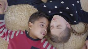 Joli gar?on d'afro-am?ricain de portrait et fille caucasienne blonde se trouvant sur le plancher sur le tapis et le regard peluch banque de vidéos