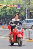 Joli gril sur un rétro e-vélo rouge de style, Kunming, Chine Photographie stock libre de droits