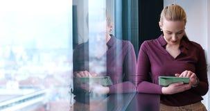 Joli immeuble de bureaux d'Using Tablet In de femme d'affaires par la fenêtre Images libres de droits