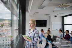 Joli immeuble de bureaux d'Using Tablet In de femme d'affaires par la fenêtre Image stock