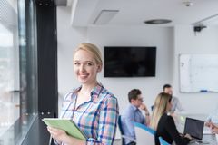 Joli immeuble de bureaux d'Using Tablet In de femme d'affaires par la fenêtre Photo stock