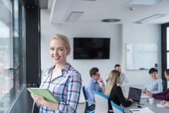 Joli immeuble de bureaux d'Using Tablet In de femme d'affaires par la fenêtre Images stock
