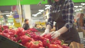 Joli jeune travailleur féminin de magasin dans un tablier brun et gant blanc sur un fond des clients banque de vidéos