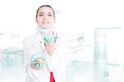Joli médecin gai t'offrant des capsules Images stock