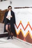Joli modèle de femme de mode utilisant un manteau foncé et un chandail blanc, dans des lunettes de soleil, posant au-dessus du fo photo stock