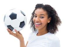 Joli passioné du football dans la boule se tenante blanche souriant à l'appareil-photo Photos stock