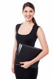 Joli secrétaire féminin retenant des fichiers d'affaires Photos stock