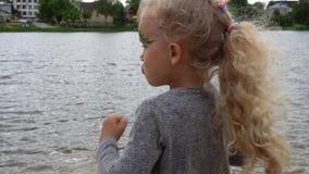Joli sourire idiot blond de fille devant la caméra sur le fond de lac Mouvement de cardan banque de vidéos
