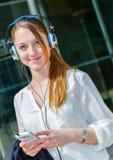 Joli travailleur écoutant la musique dans l'avant son bureau Photographie stock libre de droits
