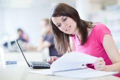 Joli étudiant féminin avec l'ordinateur portatif et les livres Photographie stock