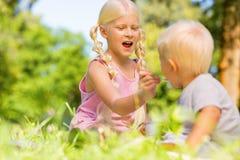 Jolie écolière alimentant un enfant en parc images stock