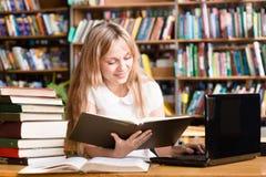 Jolie étudiante dactylographiant sur le carnet dans la bibliothèque Photographie stock libre de droits