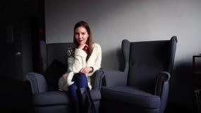 Jolie étudiante souriant et posant sur l'appareil-photo, se reposant dans le fauteuil en café élégant la soirée d'hiver banque de vidéos