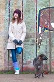 Jolie adolescente avec le crabot le jour nuageux de l'hiver Photographie stock