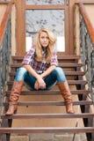 Jolie adolescente de sourire s'asseyant sur les escaliers Photographie stock libre de droits