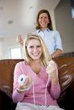Jolie adolescente jouant des jeux vidéo à la maison photo stock