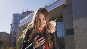 Jolie belle fille avec de longs cheveux dans des écouteurs utilisant le smartphone tout en écoutant la musique et la lecture rapi clips vidéos