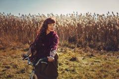 Jolie bicyclette d'équitation de fille dans le domaine Photographie stock libre de droits