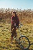 Jolie bicyclette d'équitation de fille dans le domaine Photos stock