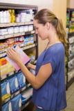 Jolie boîte de cueillette de femme dans l'étagère Photos stock