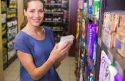 Jolie boîte de cueillette de femme dans l'étagère Photographie stock libre de droits
