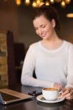 Jolie brune ayant le café utilisant l'ordinateur portable Photo libre de droits